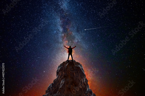 Man on top of a mountain observing the universe © quickshooting