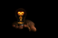 Incandescent Heart Shaped Light Bulb In Hand On Black Background For Valentine's Day