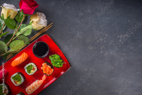 Obraz Valentine day festive dinner idea. Menu, invitation background for Valentine day sushi roll set, with heart shaped decor and rose flowers bouquet. Top view with copy space for text - fototapety do salonu