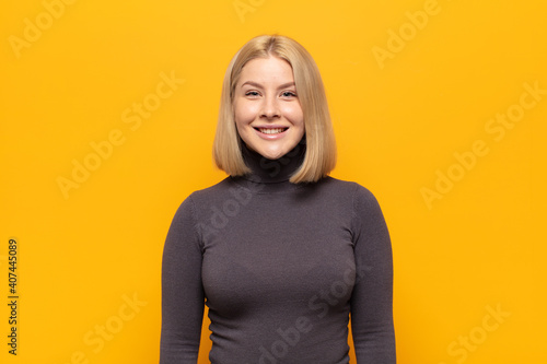 Obraz na plátně blonde woman looking happy and goofy with a broad, fun, loony smile and eyes wid