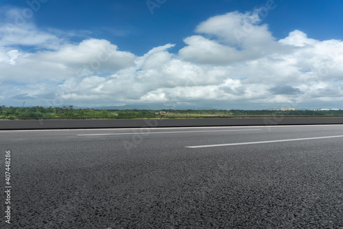 Asphalt ground and blue sky with white clouds