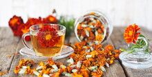 Useful Properties Of Marigolds. The Use Of Flowers Chernobrovtsy Or Mary Is Gold In Folk Alternative Medicine. Fresh Bright Flowers Of Marigolds With Dried Flowers In A Jar On A Wooden Background.
