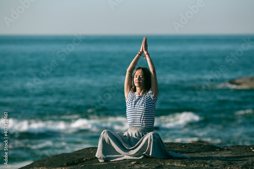 Fotografía Woman meditating on the sea beach during a wonderful sunrise