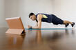 A young sports man does a plank exercise in self-isolation conditions. Online training at home with a social distance. Training all groups of mice by static load