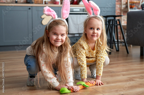 Canvas Print Two happy girls playing handmade carrots on the floor