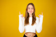 Happy beautiful young woman in white sweater is pointing up, looking away and talking. Waist up studio shot on yellow background.