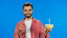 Young Bearded Man In A Red Shirt Shows Food In Hand Isolated On Blue Background.
