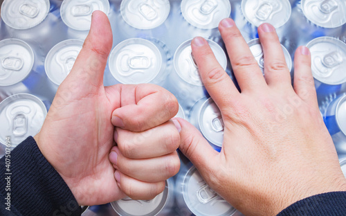 Foto Beer lover rejoices at big package of canned beer and shows thumb up