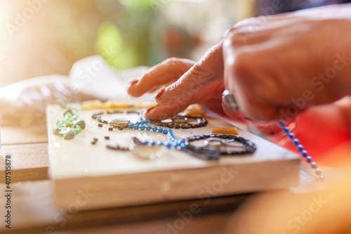 Photo grandmother making crafts with beads at home