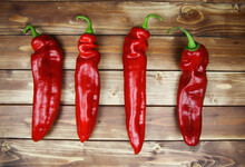 Closeup Of Isolated Group 4 Red Ripe Raw Pointed Peppers In A Row, Wood Timber Planks Background