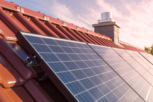 Solar Panels Or Photovoltaic Power Plant On Roof Of A House, Chimney In The Background