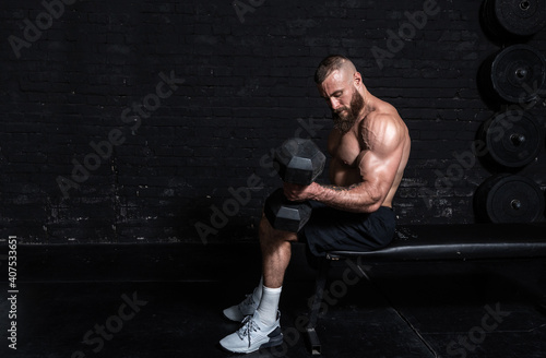 Young active strong sweaty fit muscular man with big muscles sitting on the benc Fototapeta