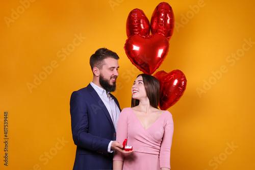 Bearded man proposing to his beautiful girlfriend on st Fototapeta