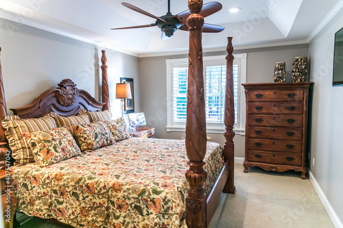 Fotografiet Small Master bedroom with a large four poster wood bed and an old fashioned floral comforter with a window