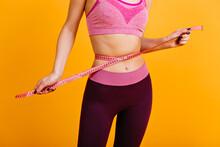 White Woman Posing With Measure Tape On Her Waist. Sporty Girl Wears Pink Sportswear.