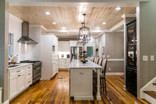 Large Renovated White Kitchen With Textured Subway Tile, Black Iron Lights And Pine Hardwood Flooring