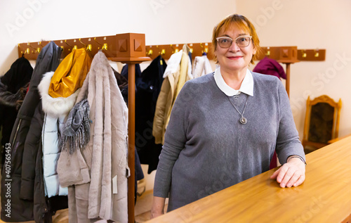 Fototapeta Female cloakroom attendant gives out clothes at the cinema