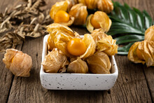 Cape Gooseberry In A White Cup Rests On An Old Wood Floor