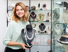 Portrait Of Happy Young Woman Demonstrating Natural Pearls And Turquoise Stone Necklace In Shop