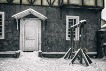 Beautiful Facade With A Door. Abandoned Building And Old Swing Nearby. Winter Snowy Day.