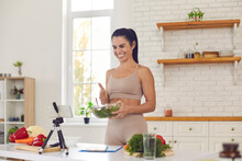 Happy Positive Fit Woman Blogger Recording Culinary Video Blog On Cellphone. Smiling Fitness Vlogger Filming Vlog About Healthy Food, Giving Dieting Tips, Sharing Cooking Advice And Vegan Salad Recipe