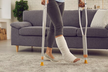 Young Patient Undergoes Rehabilitation At Home. Woman With Broken Leg In Cast Makes Good Progress And Walks With Crutches In The Living-room. Domestic Life And Successful Recovery After Car Accident
