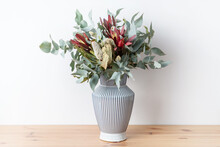 Beautiful Flower Arrangement Of Mostly Australian Native Flowers, Including Banksia, Silvan Reds And Eucalyptus Leaves, In A White And Blue Strip Vase, With A White Background On A Wooden Table.