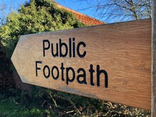 A Wooden Public Footpath Direction Sign In A Rural Uk Location