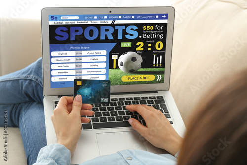 Fotografia Young woman with credit card placing sports bet at home