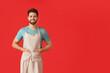 Leinwandbild Motiv Young man wearing apron on color background
