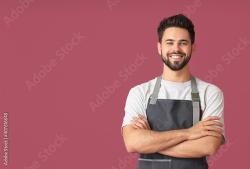 Fototapeta Young man wearing apron on color background obraz