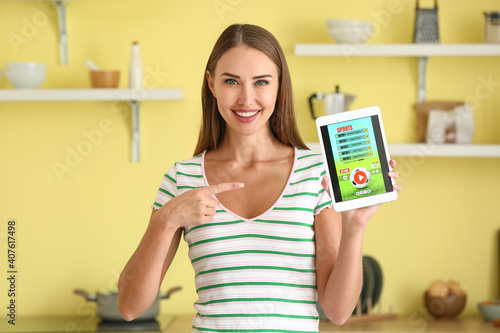 Foto Beautiful woman placing sports bet in kitchen