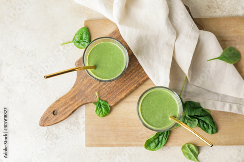 Glasses of healthy spinach smoothie on light table © Pixel-Shot