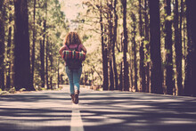 Travel People Alternative Backpack Freedom Concept With Woman Walking Alone In The Middle Of The Asphalt Road And Forest Woods In Background - Backpacker Lifestyle And Wanderlust
