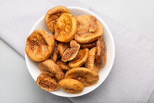 Bowl With Tasty Dried Figs On Light Background