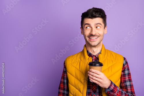 Photo of cute cheerful young guy dressed yellow vest holding brown cup looking empty space isolated purple color background © deagreez