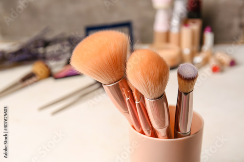 Fototapeta Cup with makeup brushes on table, closeup obraz na płótnie