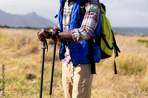 Fotografie, Obraz Fit african american man wearing backpack nordic walking on coast