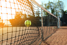 Bright Yellow Tennis Ball Hitting Into Net On Court
