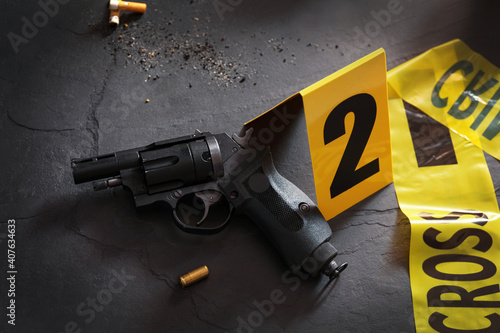 Composition with gun and shell casing on black slate table Fototapeta