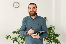 Smiling Young Bearded Man In Office Making Notes In Planner.