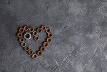 Heart Made Of Small Rusty Nuts. Machine Parts. Items On A Dark Background.