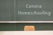 Wort Corona Homeschooling an einer grünen Tafel
