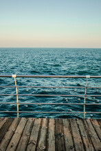Old Wooden Rustic Pier With Metal Handrail. Blue Cold Sea View Skyline. Winter Seascape. Central Composition. Concept Of Enjoying Nature, Nobody, Loneliness, Freedom, Tranquility, Dreaming, Thinking