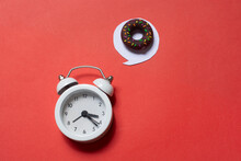High Angle Shot Of An Alarm Clock And A Chocolate Donut On A Red Surface