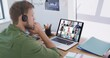 Caucasian man using laptop and phone headset on video call with colleagues