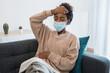 Black girl having flu, feeling bad and lying on the sofa