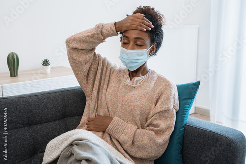 Black girl having flu, feeling bad and lying on the sofa Wallpaper Mural