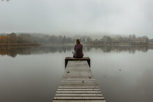 Calm Morning Relaxation By The Foggy Pond. Sitting Woman In The Countryside. Intended Female Mysterious Atmosphere. Autumn Afternoon In The Nature. Silence. Wooden Pier On A Pond.
