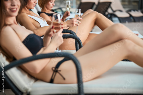 Fotografia Cropped photo of three girlfriends in swimsuits resting on sunbeds